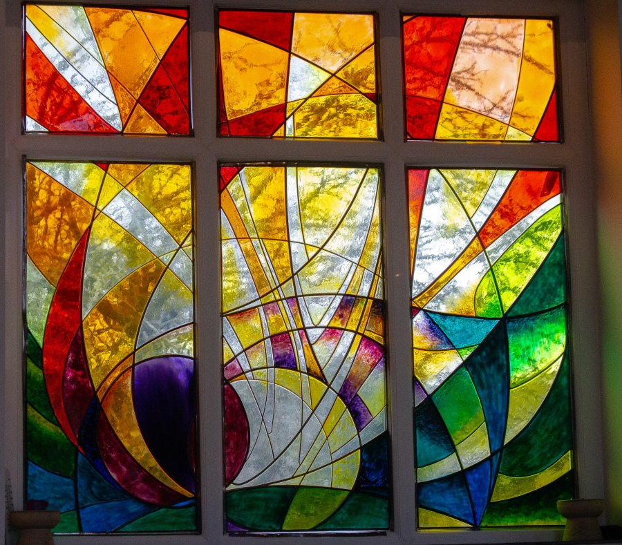 Modern stained glass window, reds, oranges and yellows.