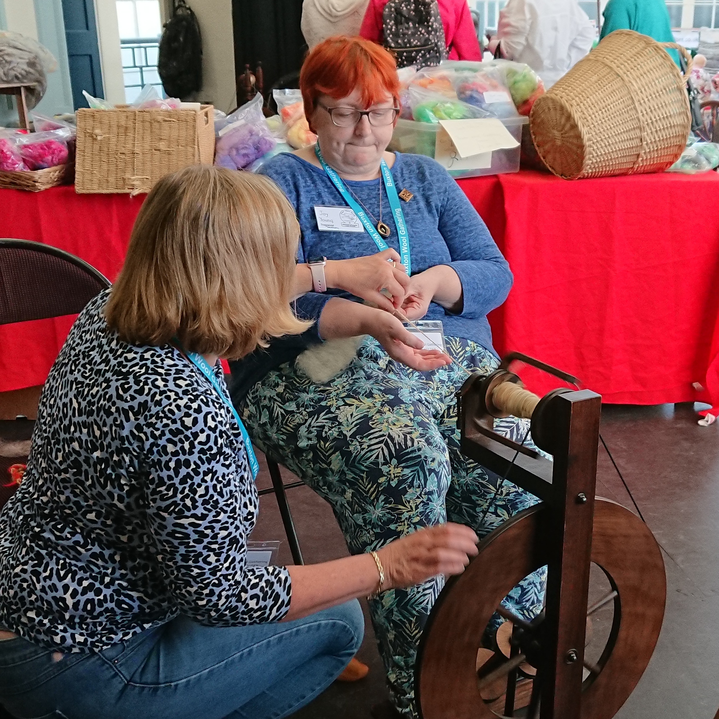 Two women sit next to a spinning wheel, one facing the wheel whilst the other, with bright red hair and a very determined face, is trying to learn to spin.