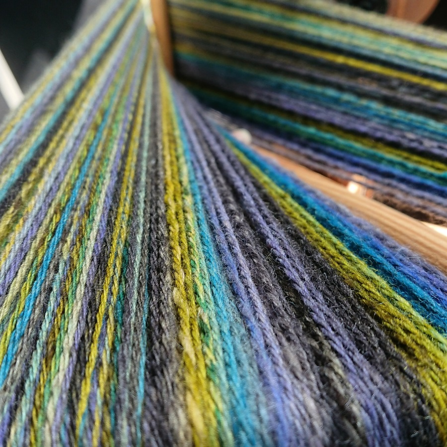 Image of multicoloured handspun yarn on a niddy noddy - vibrant mustard green, blue and dark grey.